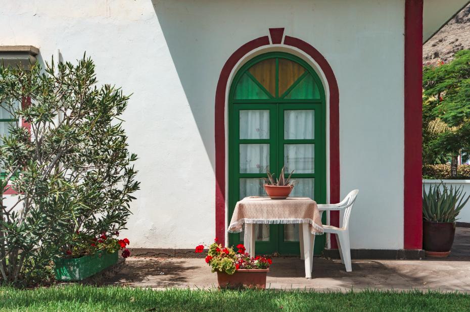 Devant de maison en bord de mer avec table de jardin et fleurs rouges