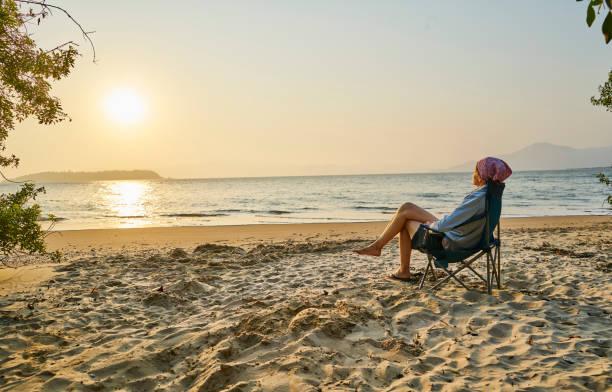 Femme sur un stransat au soleil à la plage en vacances